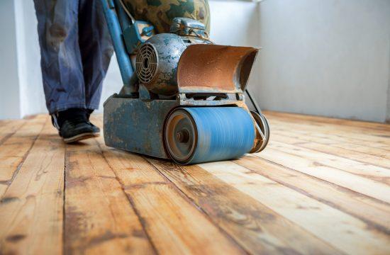 Mężczyzna cyklinujący podłogę